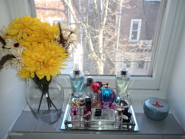 Her Philly; Decorating ideas for a bathroom shelf in a small city apartment featuring flowers, a vintage glass tray, perfume and a candle.
