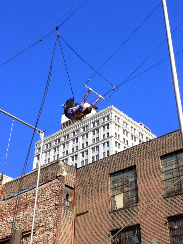 Flying on the trapeze during the PIFA Daringly High Trapeze Class, taught by Fly School Circus Arts, on Broad Street in Philadelphia all April long / Her Philly