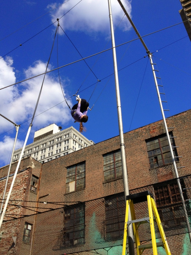 Hanging upside down on the trapeze during the PIFA Daringly High Trapeze Class, taught by Fly School Circus Arts, on Broad Street in Philadelphia all April long / Her Philly